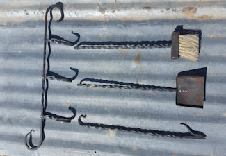Hand forged fireplace tools, including broom, dustpan, and fire poker
