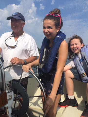 sailing the Shrewsbury River for dyslexia group of 3 people steering a boat