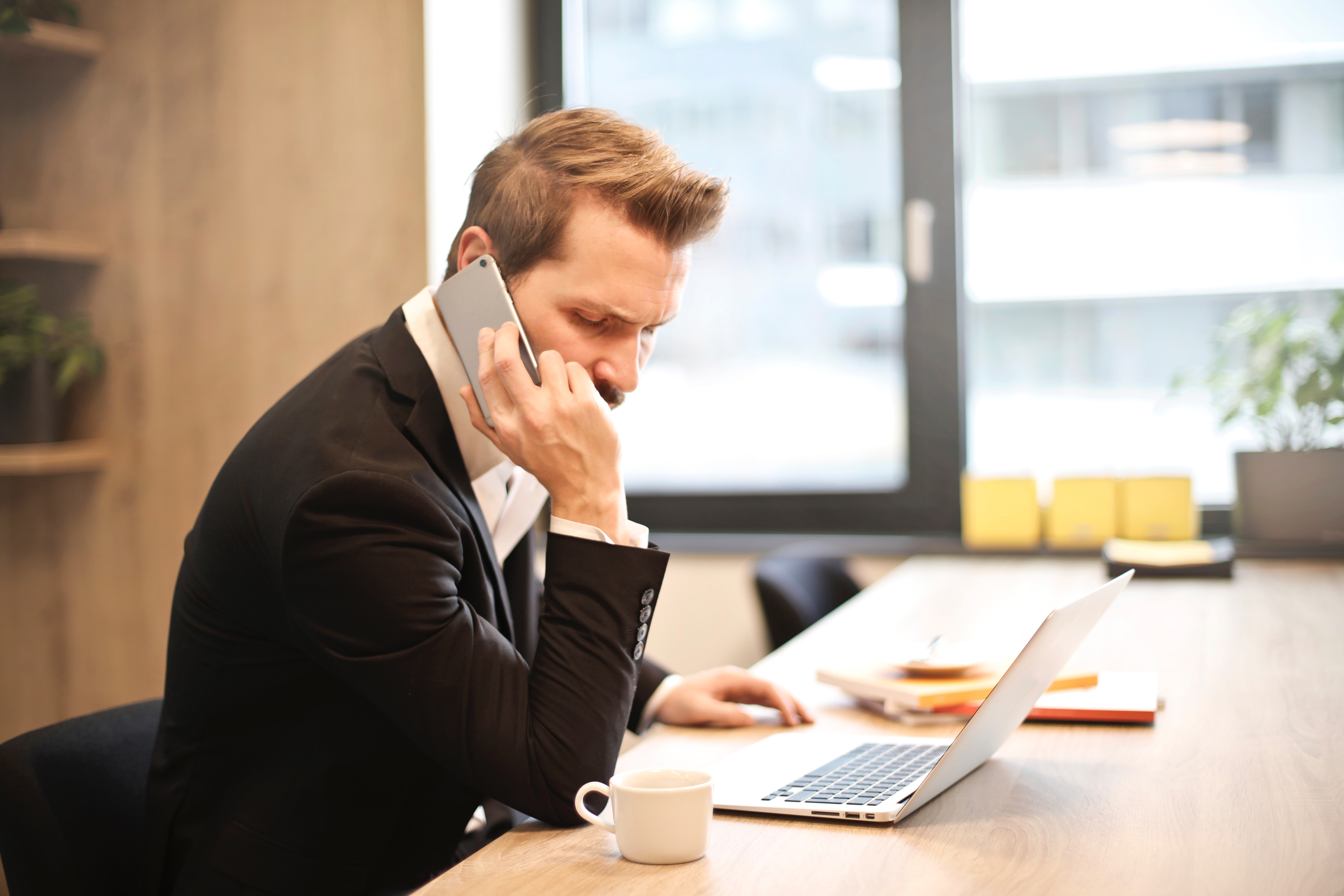 Man having a phone call in front of a laptop