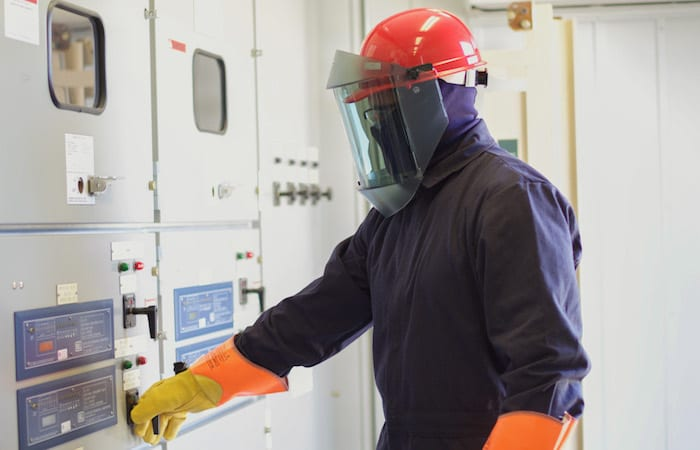 Worker wearing PPE reaching electrical unit