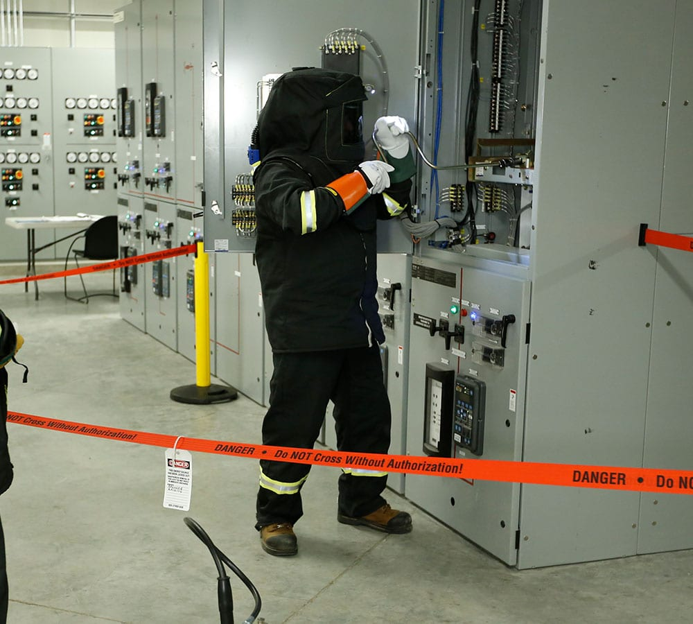 Worker behind caution tape and working on electrical machine