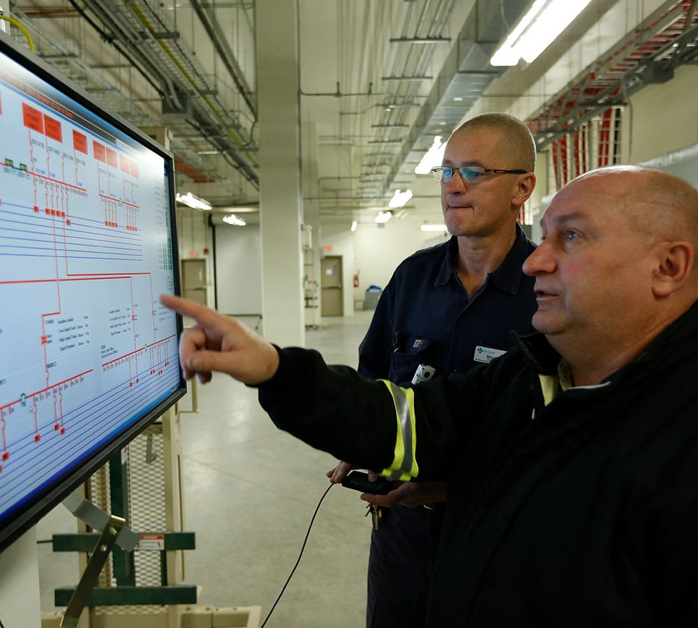 Instructor pointing on screen to learner in industrial setting