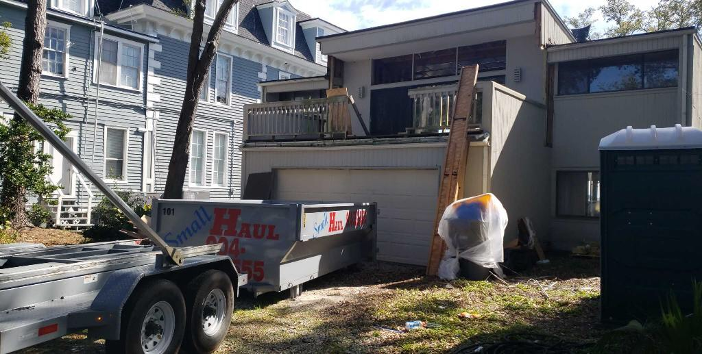 Roll off dumpster by garage