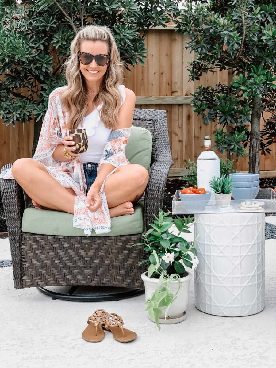 low calorie cocktails | Low Calorie Cocktail Recipes by popular Houston lifestyle blog, Haute and Humid: image of a woman holding a Nordstrom Corkcicle glass and sitting in a patio chair next to a end table with some Anthropologie latte bowls and a Nordstrom Wine Chiller VINGLACÉ on it.