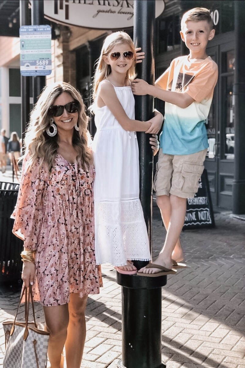 mother's day gift | Galveston Travel Guide by popular Houston travel blog, Haute and Humid: image of a mom wearing a Amazon Milumia Womens Floral Print Front Cross Deep V-Neck Flare Sleeve Loose Short Mini Dress, Amazon NEWNOVE Handmade Raffia Earrings Lightweight Geometric Straw Dangle Earrings for Women, Nordstrom Quay Australia sunglasses, and Amazon BuDhaGirl Gold All Weather Bangles and standing next to her two kids as they stand on a black lamp post.