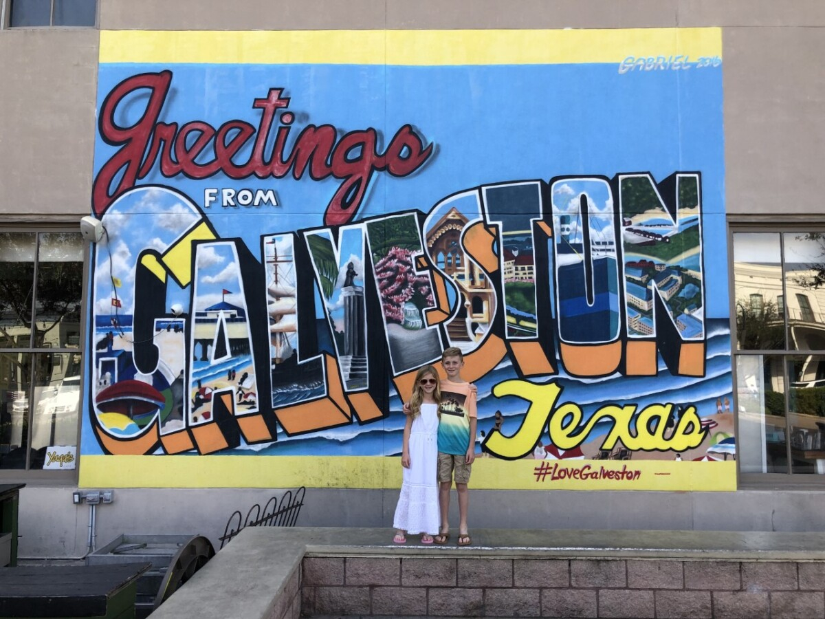 Galveston Travel Guide by popular Houston travel blog, Haute and Humid: image of two kids standing in front of a greetings from Galveston Texas sign.