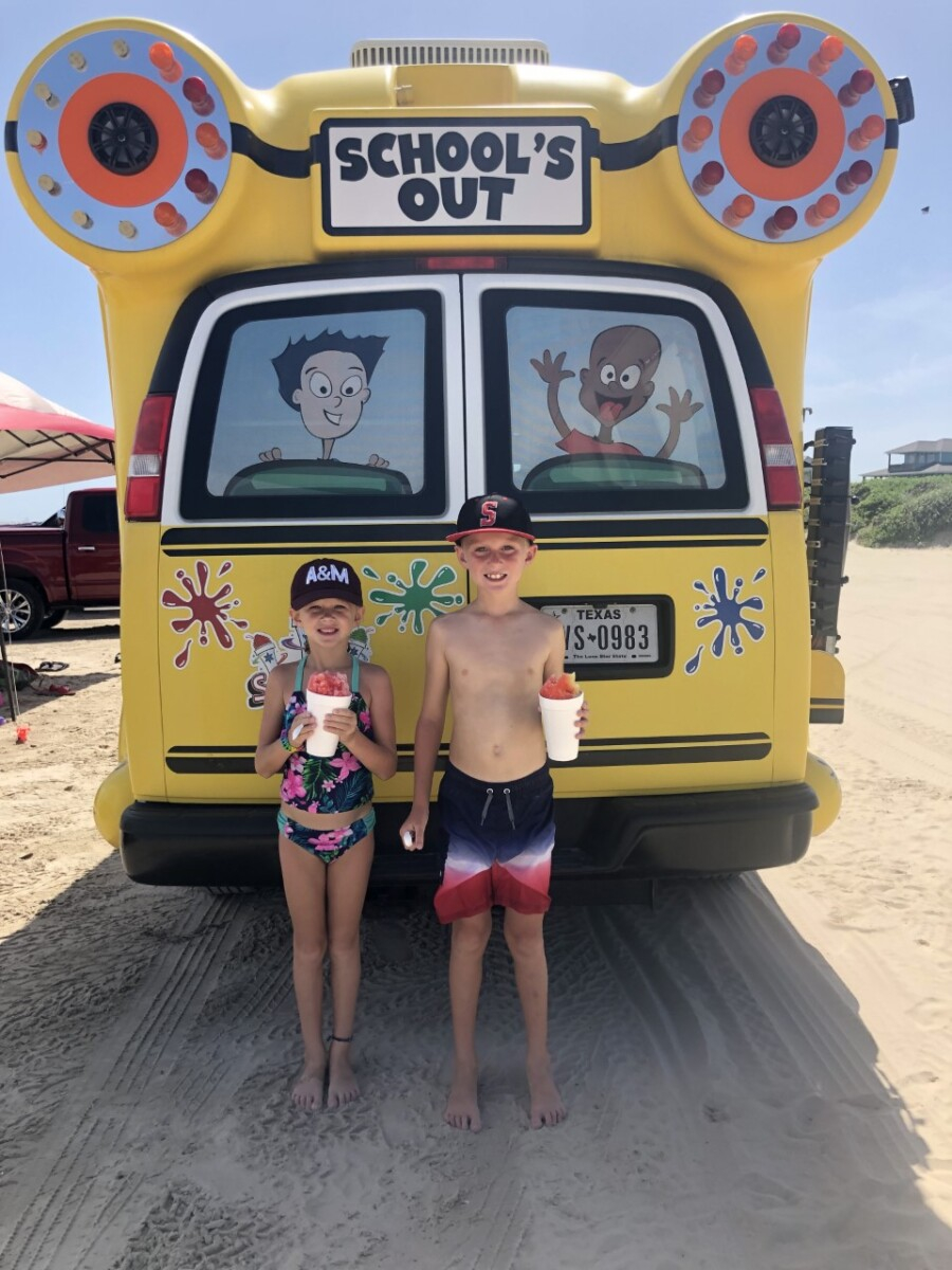 galveston beaches | Galveston Travel Guide by popular Houston travel blog, Haute and Humid: image of two kids wearing swimsuits and eating snow cones on a Galveston Texas beach.