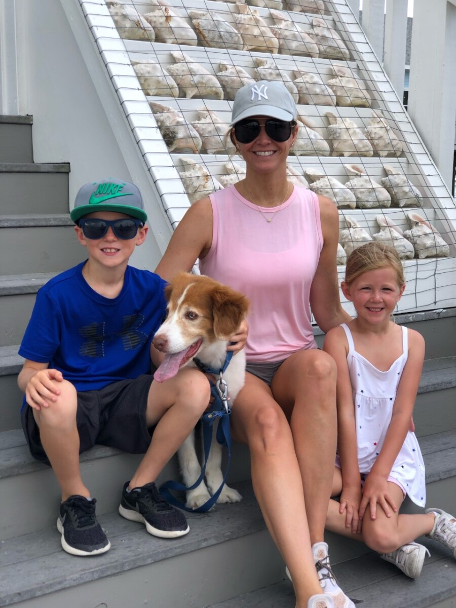 galveston travel guide | Galveston Travel Guide by popular Houston travel blog, Haute and Humid: image of a mom, her two kids, and a dog sitting on some steps outside next to a conch shell display.