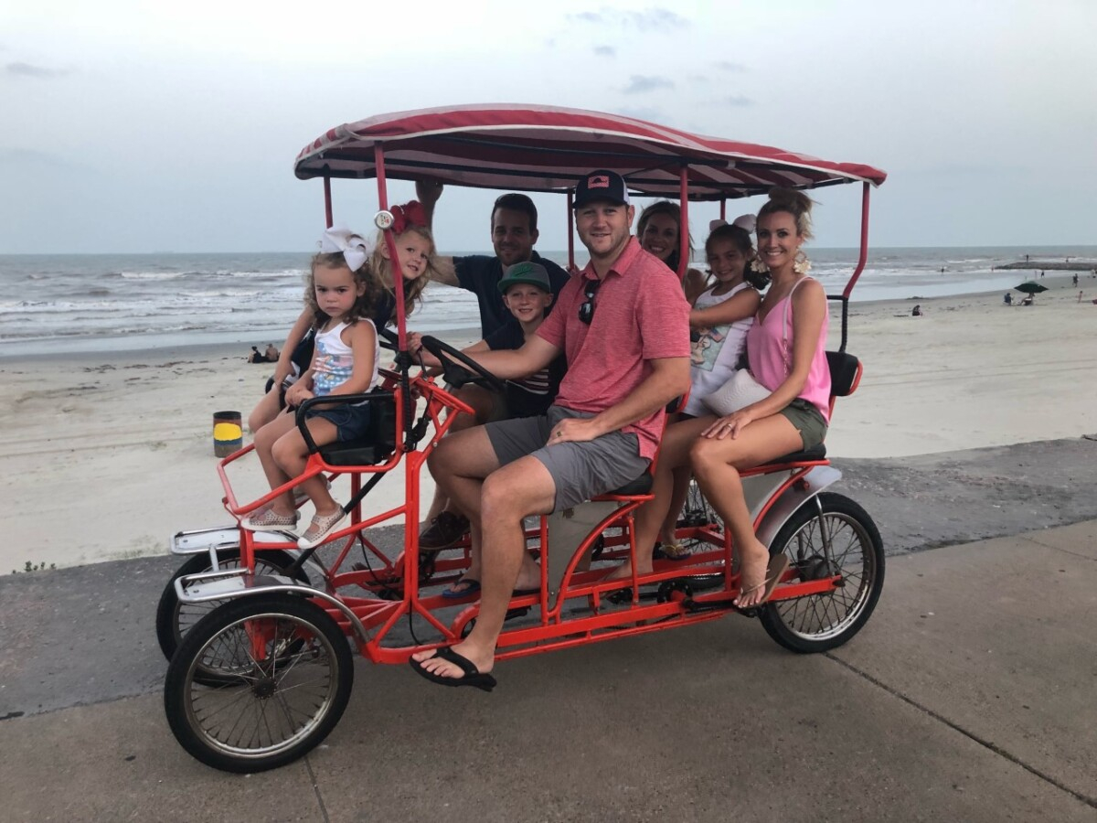 galveston bike rentals | Galveston Travel Guide by popular Houston travel blog, Haute and Humid: image of a family riding a bike cart on a Galveston, Texas beach.