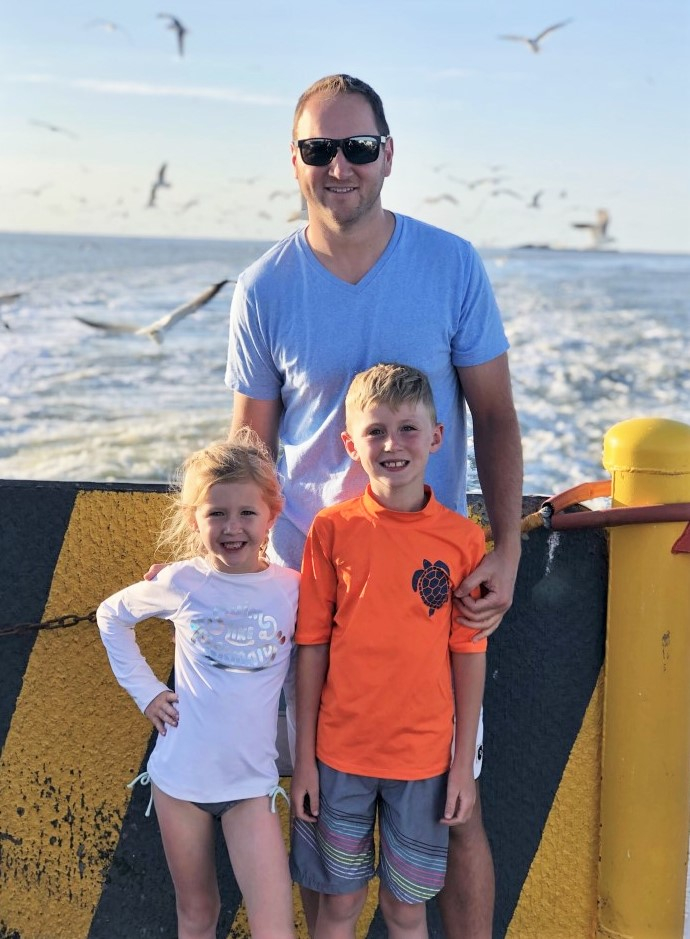 father's day gift guide | Father' Day Gift Ideas by popular Houston lifestyle blog, Haute and Humid: image of a dad standing with his son and daughter on a ferry.