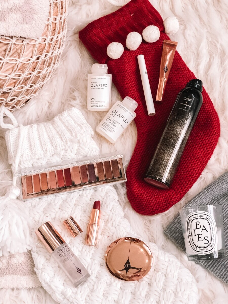 stocking stuffers for her  Stocking Stuffer Ideas by popular Houston life and style blog, Haute and Humid: image of Charlotte Tilbury makeup, Olaplex hair care, and a white and red stocking.