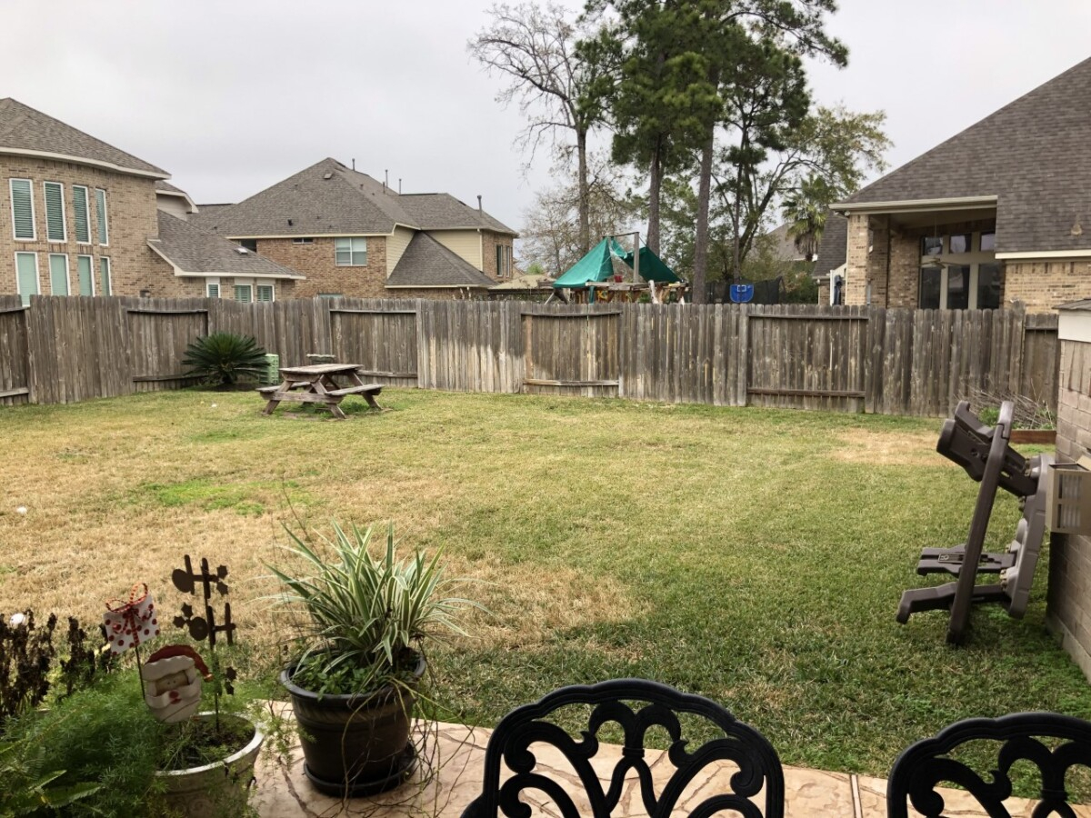 pool before and after   Outdoor Kitchen by popular Houston life and style blog, Haute and Humid: image of a backyard with grass, wooden picnic table, and wooden fence.