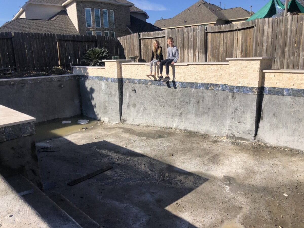 pool build   pool dig   pool before and after   Outdoor Kitchen by popular Houston life and style blog, Haute and Humid: image of two kids sitting on the edge of an unfinished pool.