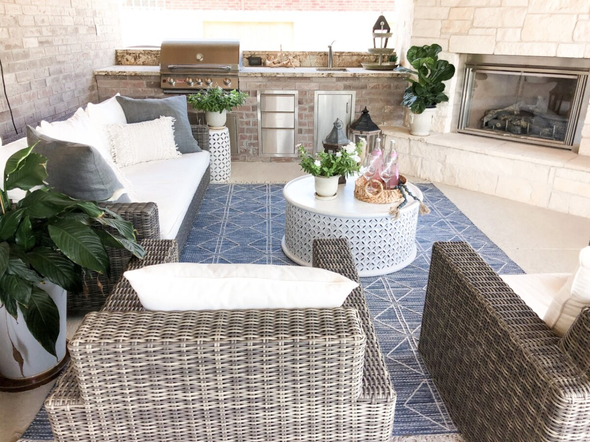 outdoor living area   Outdoor Kitchen by popular Houston life and style blog, Haute and Humid: image of a wicker patio set with white cushions, blue and white area rug, round white coffee table, and outdoor plants.