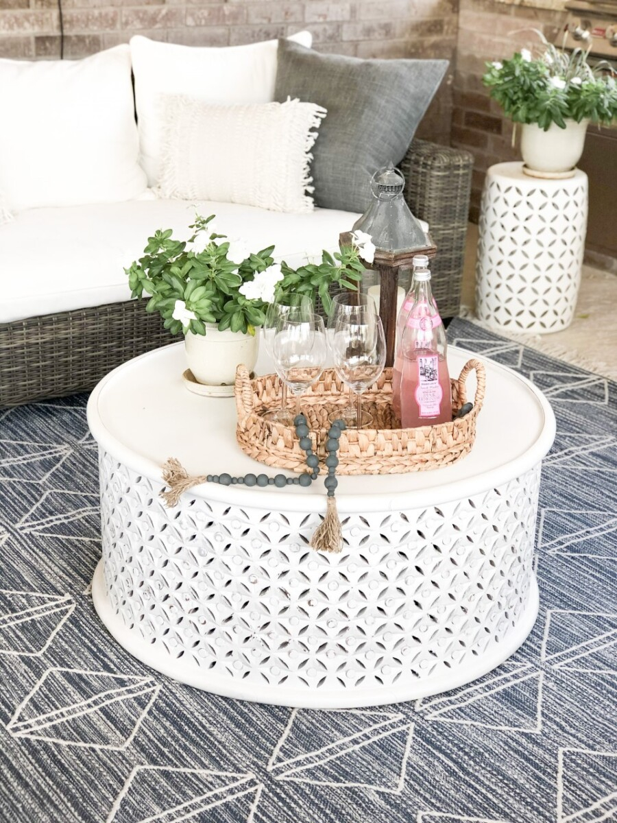 coffee table   Outdoor Kitchen by popular Houston life and style blog, Haute and Humid: image of a wicker patio set with white cushions, blue and white area rug, round white coffee table, and outdoor plants.