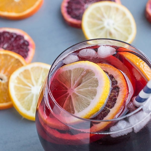 sangria | Pitcher Cocktails by popular Houston lifestyle blog, Haute and Humid: image of a sangria drink in a clear glass cup with a blue and white stripe straw.