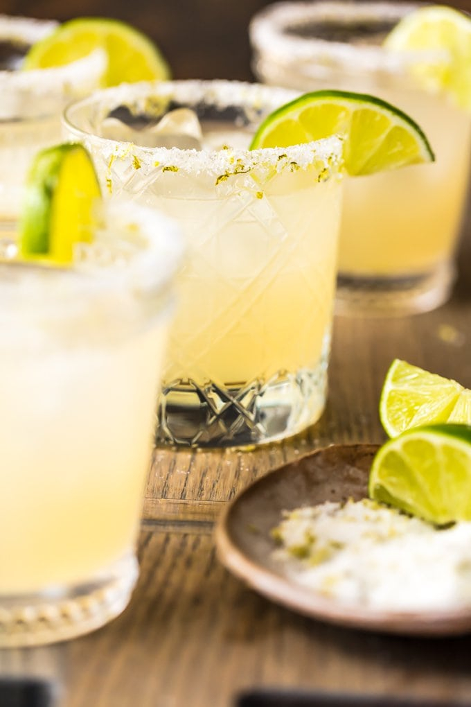 margaritas | Pitcher Cocktails by popular Houston lifestyle blog, Haute and Humid: image of margaritas in clear glasses with lime wedges and salt spread around the rim of the cup.