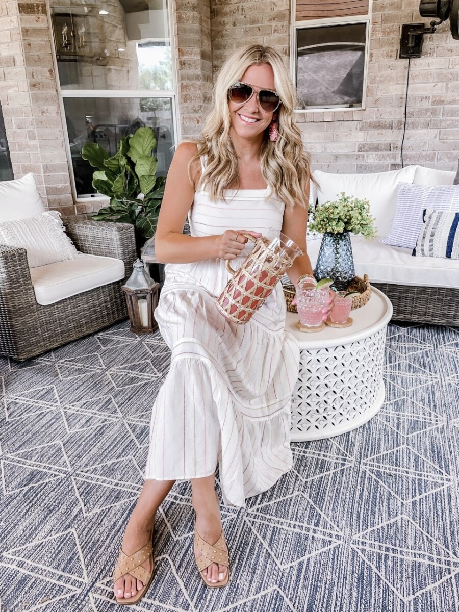pitcher cocktails | Pitcher Cocktails by popular Houston lifestyle blog, Haute and Humid: image of a woman wearing a white stripe maxi dress, pink statement earrings, sunglasses, tan gold studded cross strap slide sandals and sitting on a white metal coffee table on her patio and holding a glass cup and glass pitcher covered in raffia that's filled with a pink cocktail drink.