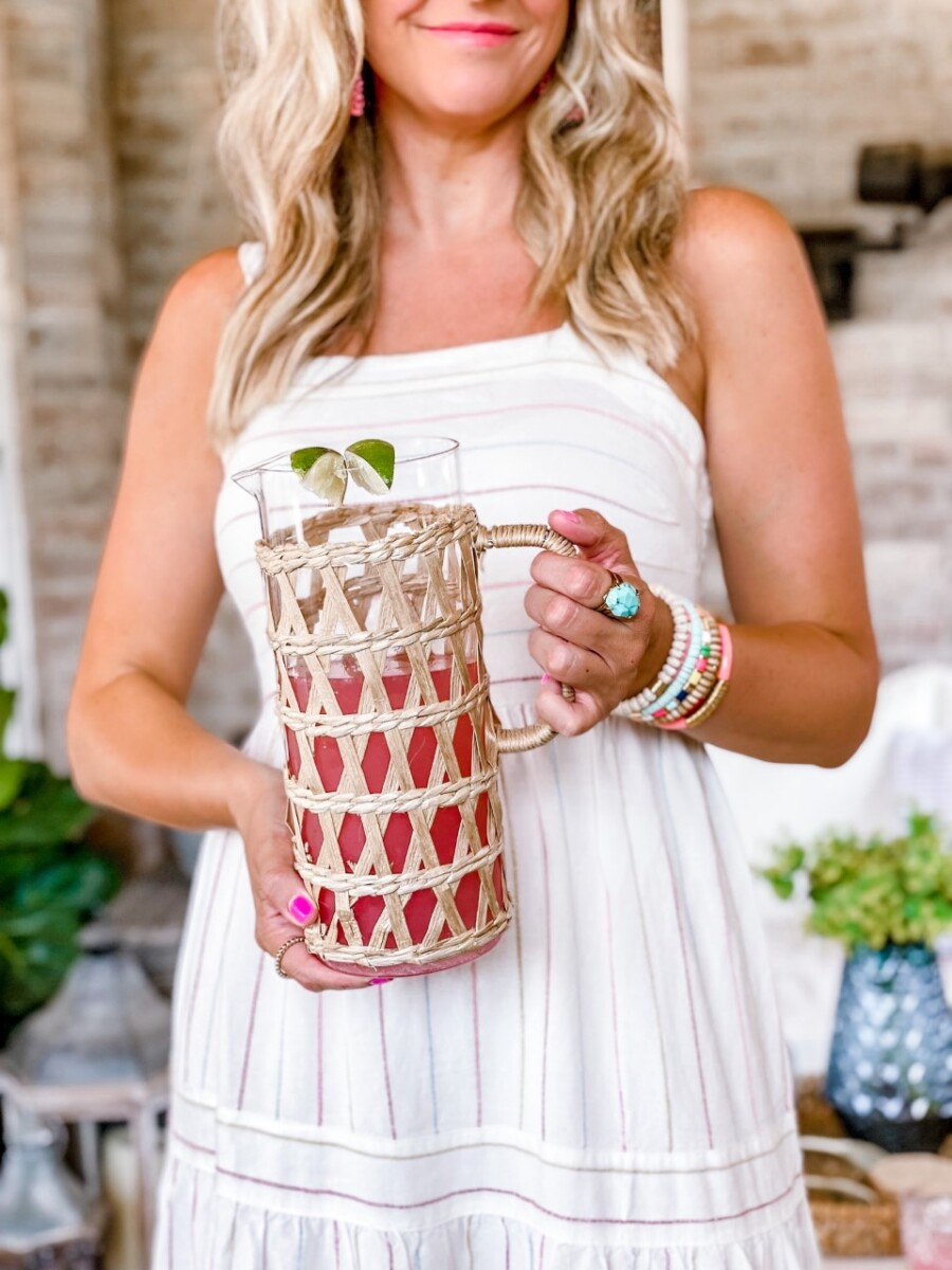 summer cocktails | Pitcher Cocktails by popular Houston lifestyle blog, Haute and Humid: image of a woman wearing a white stripe maxi dress, pink statement earrings, sunglasses, tan gold studded cross strap slide sandals and holding a glass pitcher covered in raffia that's filled with a pink cocktail drink.