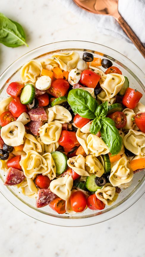 pasta salad | Summer Side Dishes by popular Houston lifestyle blog, Haute and Humid: image of cheesy tortellini pasta salad in a clear glass bowl.