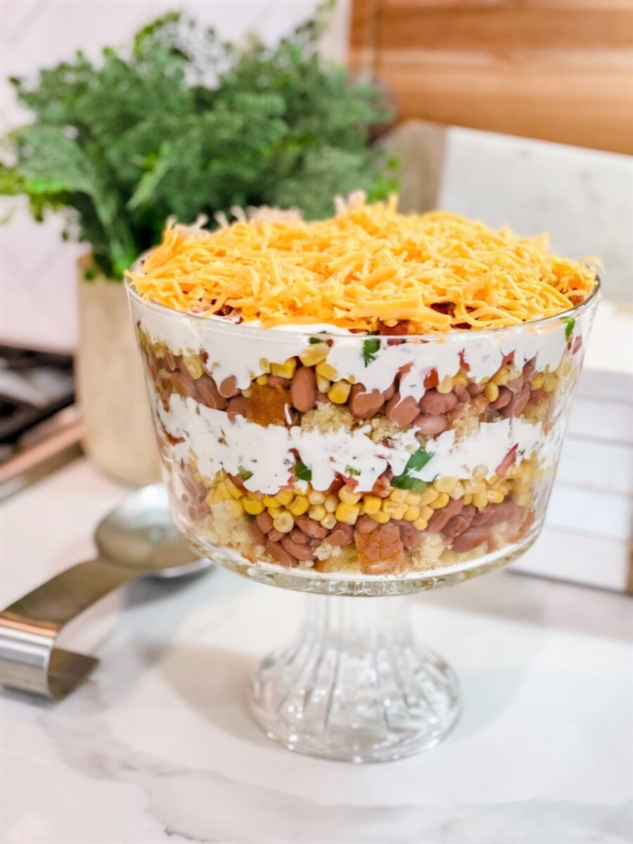 cornbread casserole | Summer Side Dishes by popular Houston lifestyle blog, Haute and Humid: image of a cornbread salad in a clear glass trifle dish.