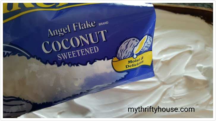 Coconut poke cake covered with Angel Flake Coconut