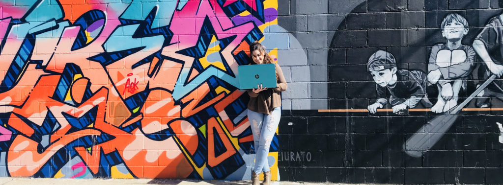 smiling woman stands in front of wall of graffiti