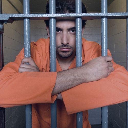 An inmate staring at the camera while behind bars.