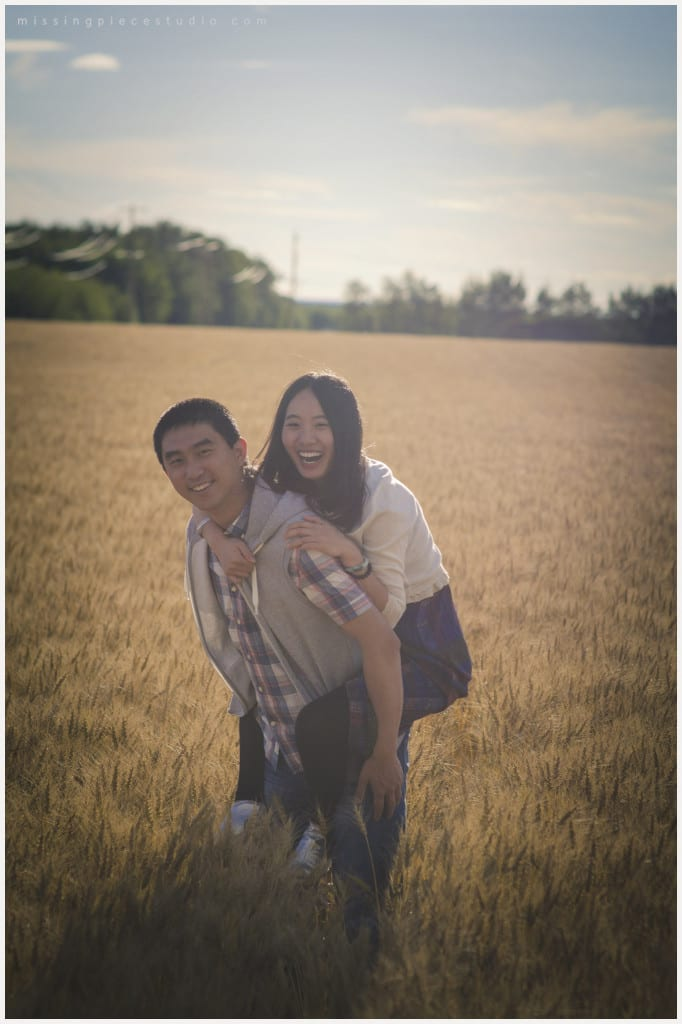 guy gives a piggy back to the girl in a beautiful field
