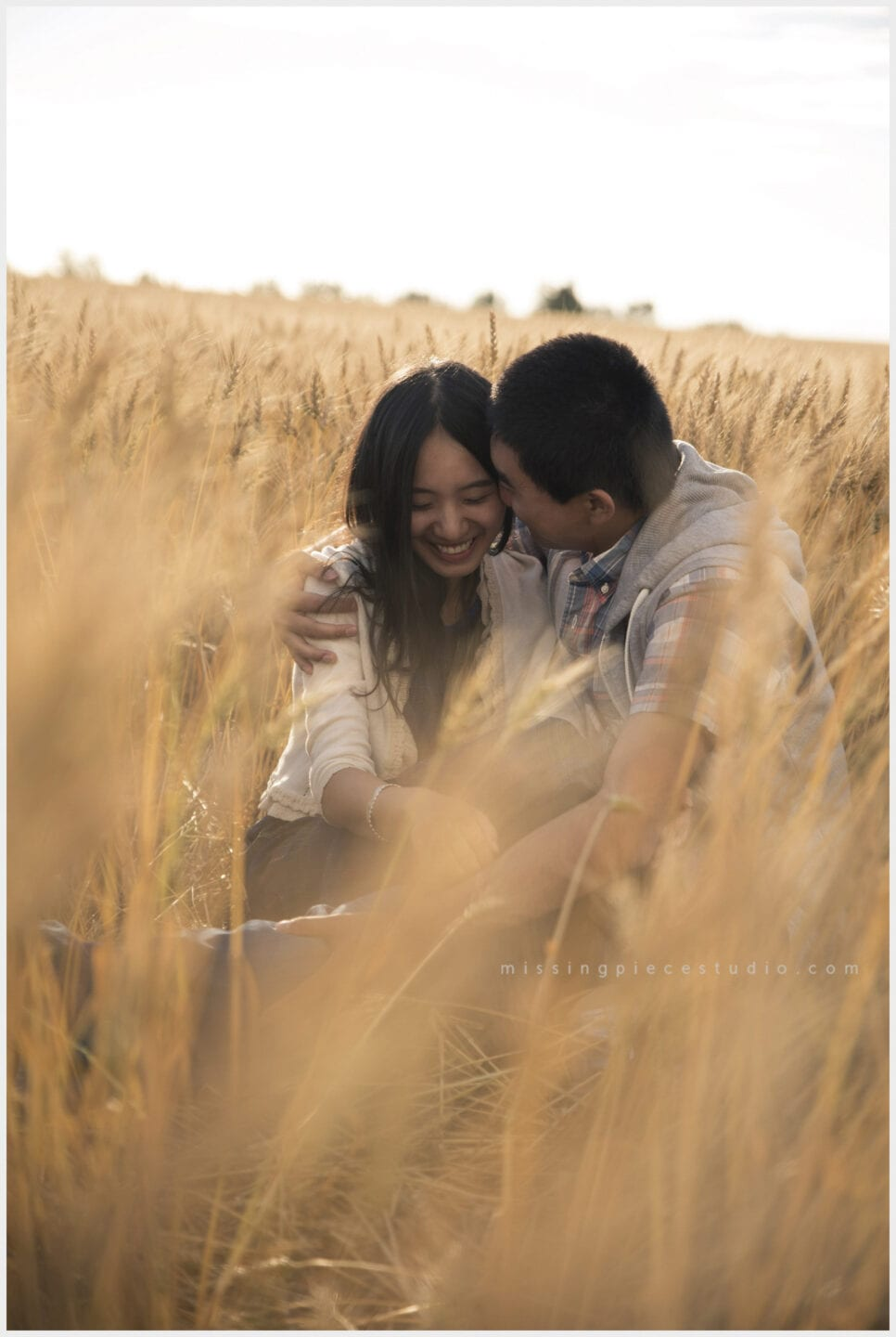 a couple whispering into each other at a picnic in a wheat field