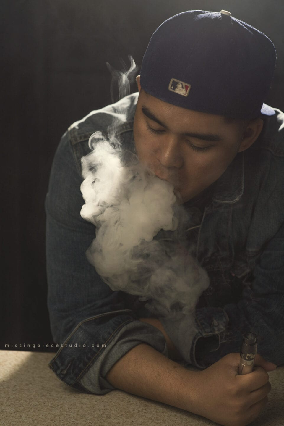 A male blowing out huge cloud of smoke called cloud chasing