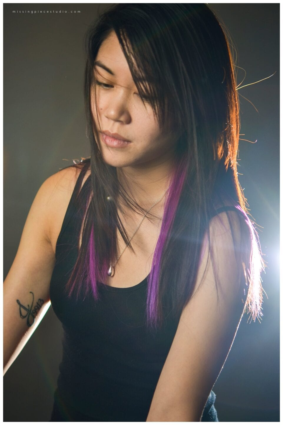 Female model with purple streaks and a tattoo on right arm