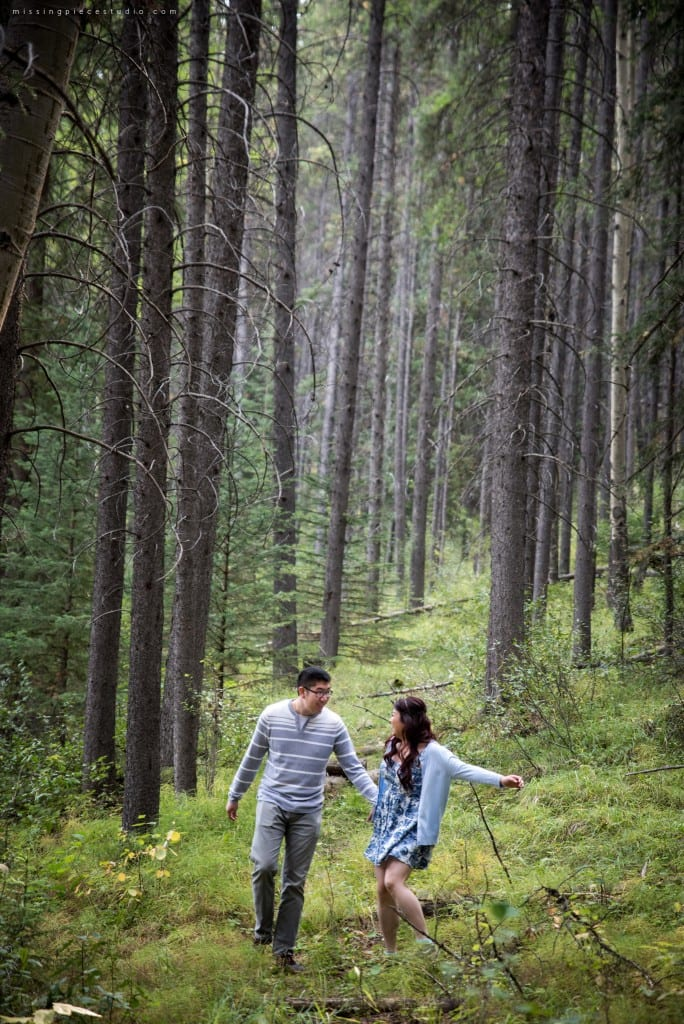 A couple running down the Banff forest in the summer near Calgary, Canada.