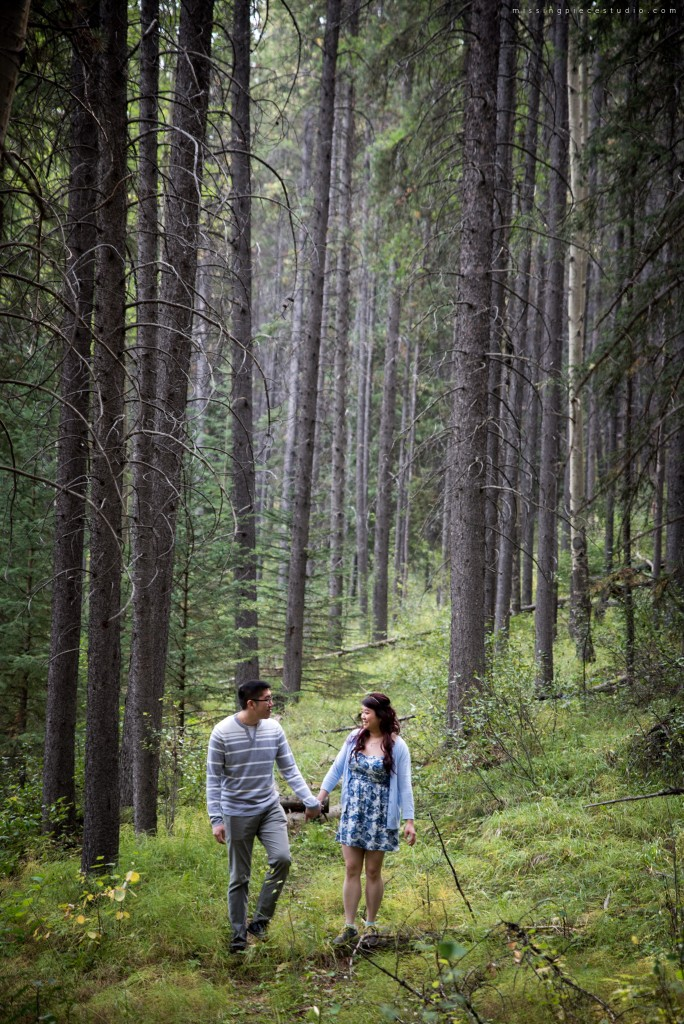 A couple running down the Banff forest in the summer near Calgary Canada