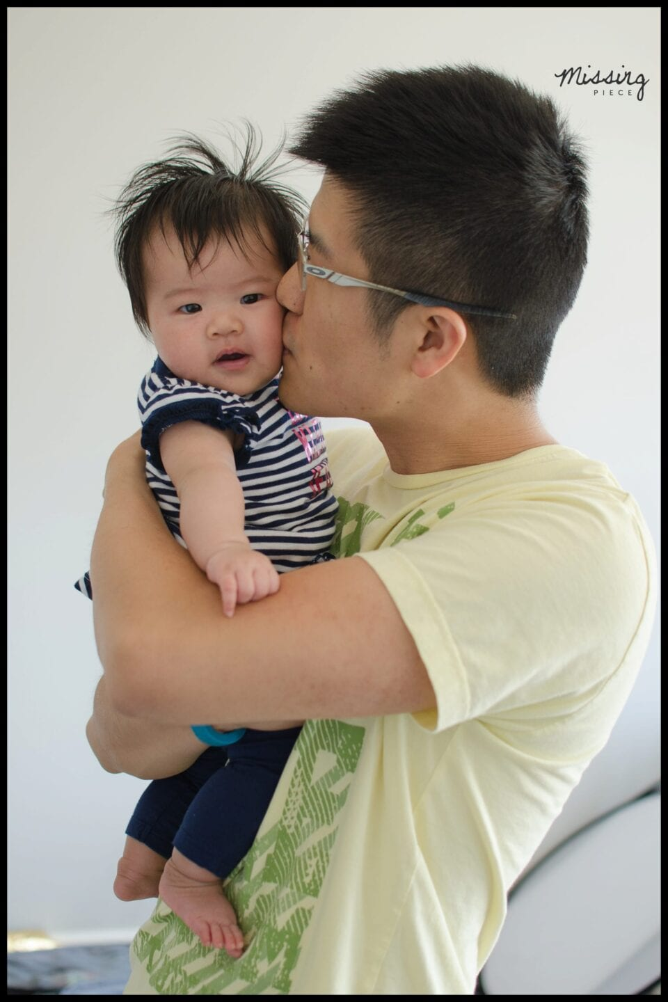 A father kisses his baby girl on the cheek.