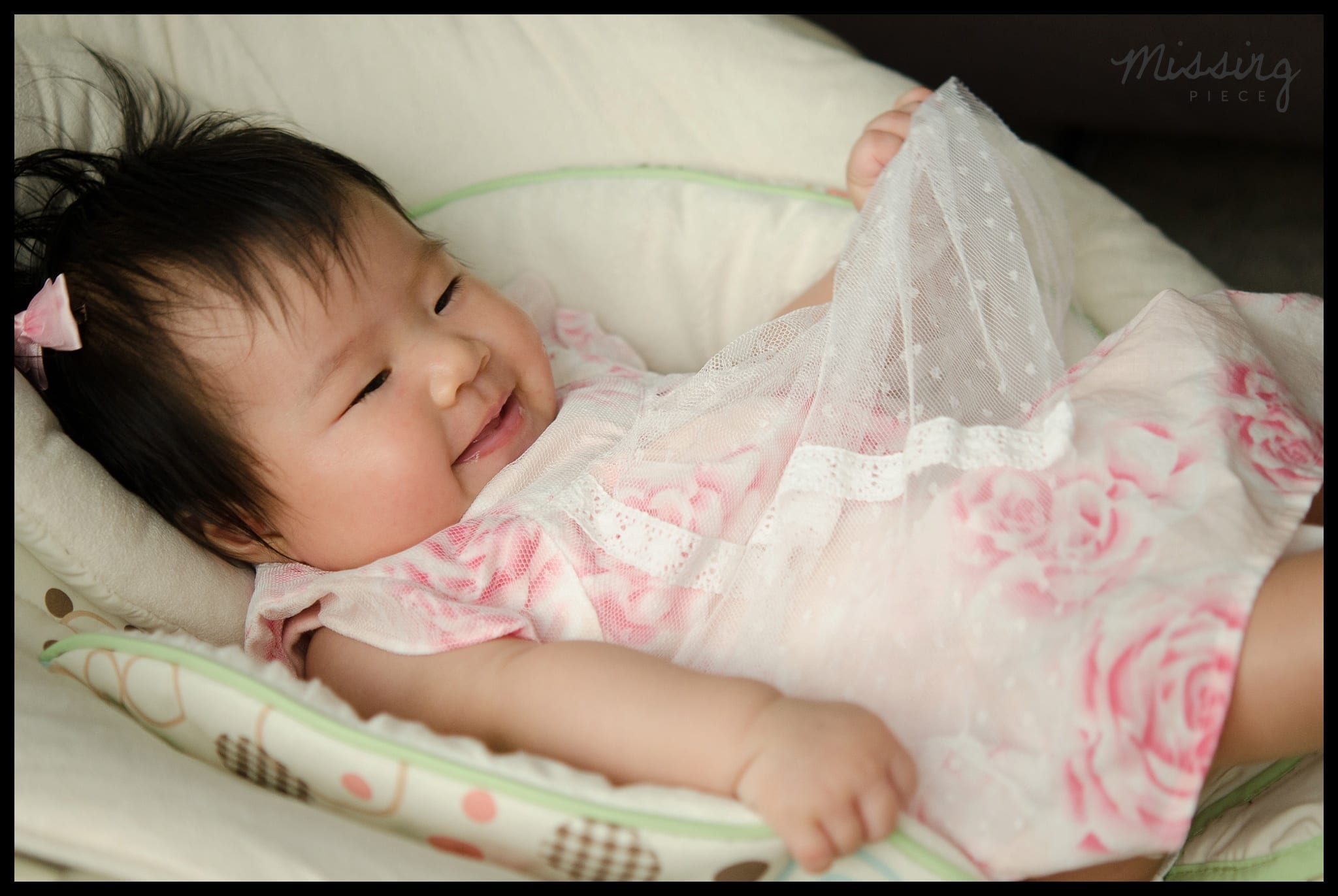 A cute baby girl smiles as she plays with her dress while laying on her crib