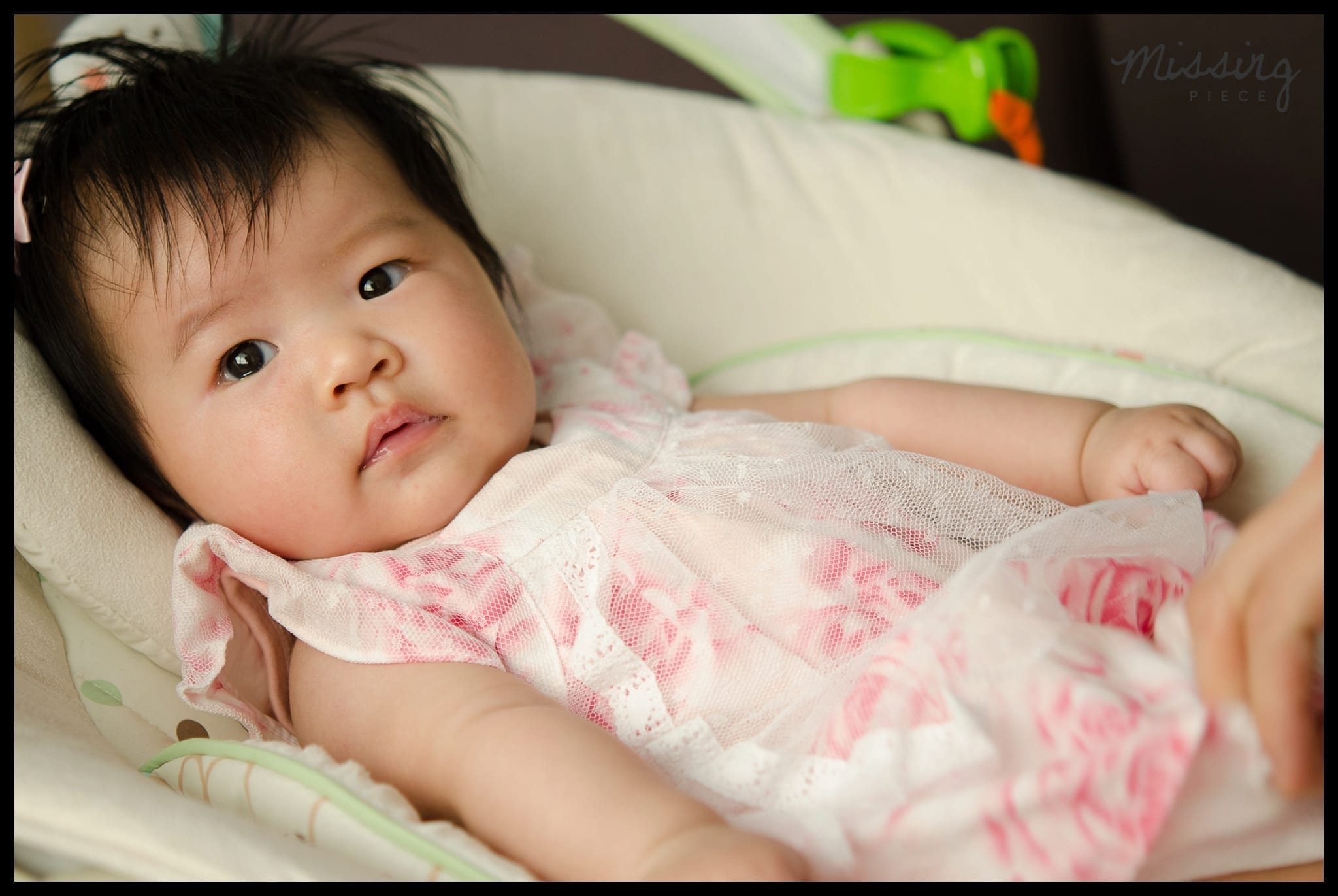 Baby looks at the camera as she sits on her crib