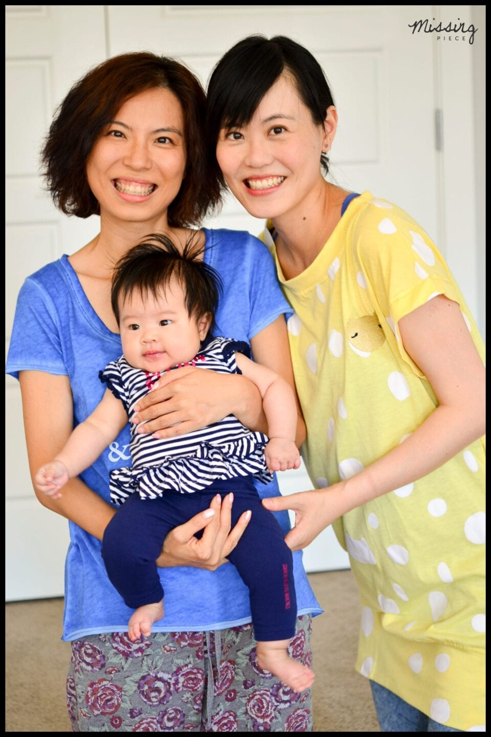 Two sisters carries the baby in a family portrait