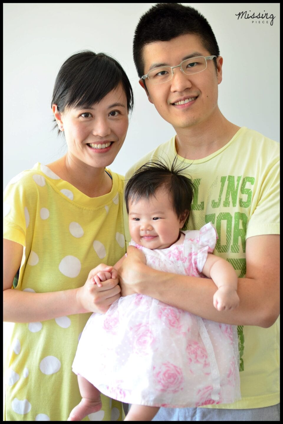 Mother and father smiles for a picture with their baby in their hands