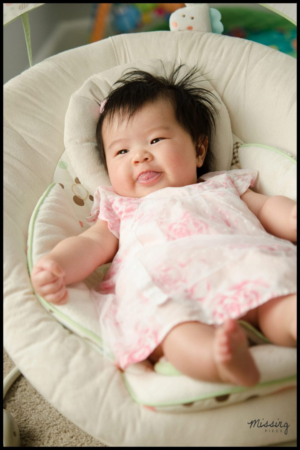 A baby sits on a crib beside a soft lit window with a gentle smile