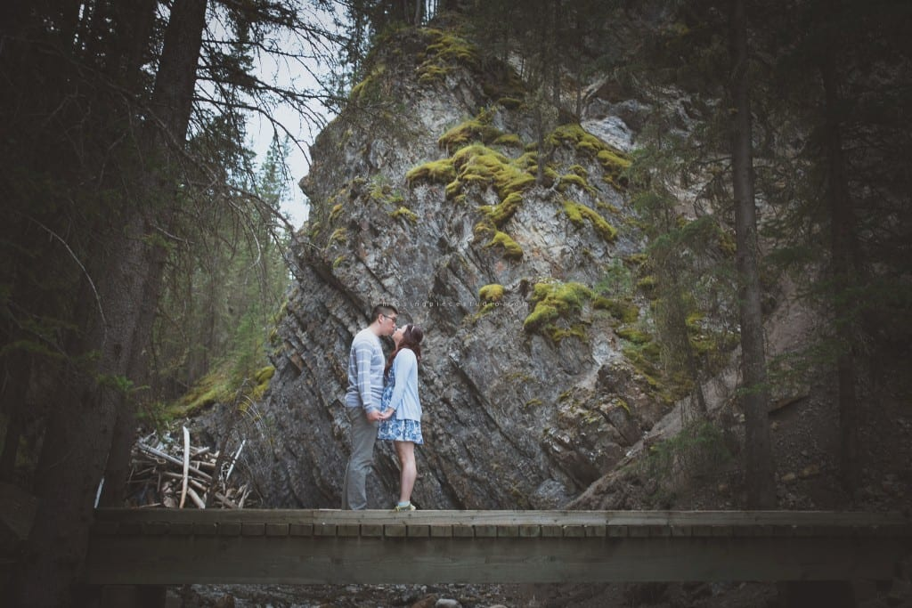 A couple kissing on a bridge at a Banff forest in the summer near Calgary, Canada.