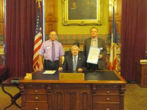 Governor Terry Branstad presents Regis Zweigart, ACS, ALB, Area 34 Director for District 19, and Paul Wood, DTM, Immediate Past District 19 Director, with the signed proclamation that October is Toastmasters Month