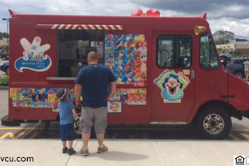 man and boy standing at window of red ice cream truck