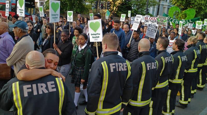 A demonstrator hugs a firefighter at a Grenfell vigil