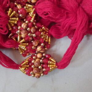 Red thread round om bead rakhi