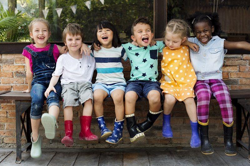 Comp - Kindergarten-kids-friends-arm-around-sitting-smiling