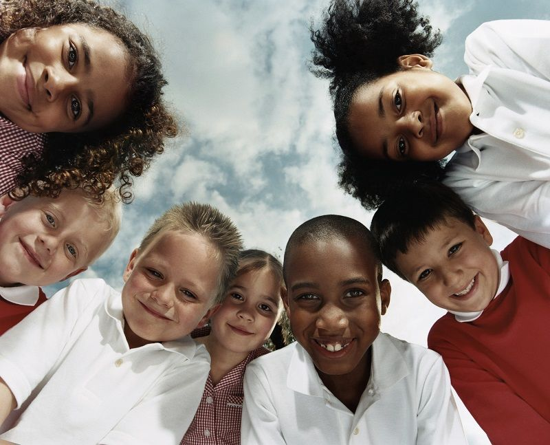 Comp-View-Directly-Below-of-Seven-Primary-School-Children-Huddled-Together-Looking-at-the-Camera