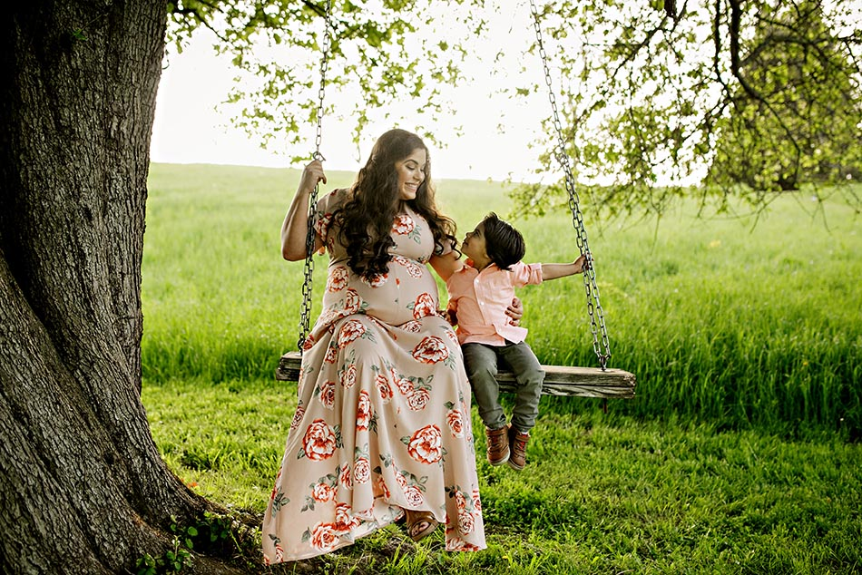 pregnant mom with child on swing