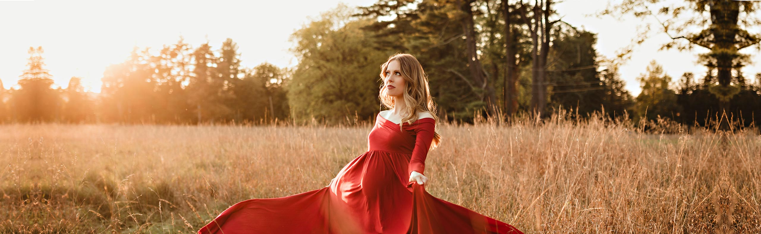 pregnant woman in red dress standing in field