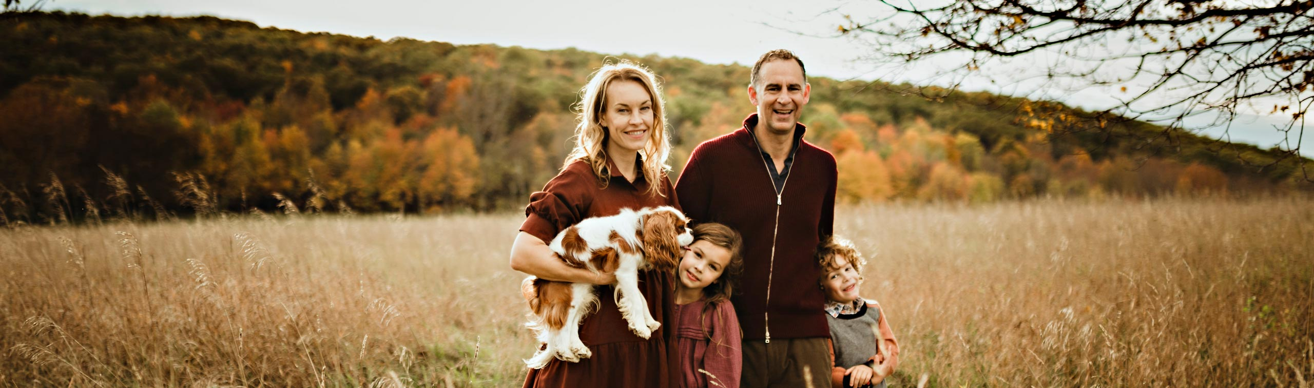 family standing with dog standing in a field